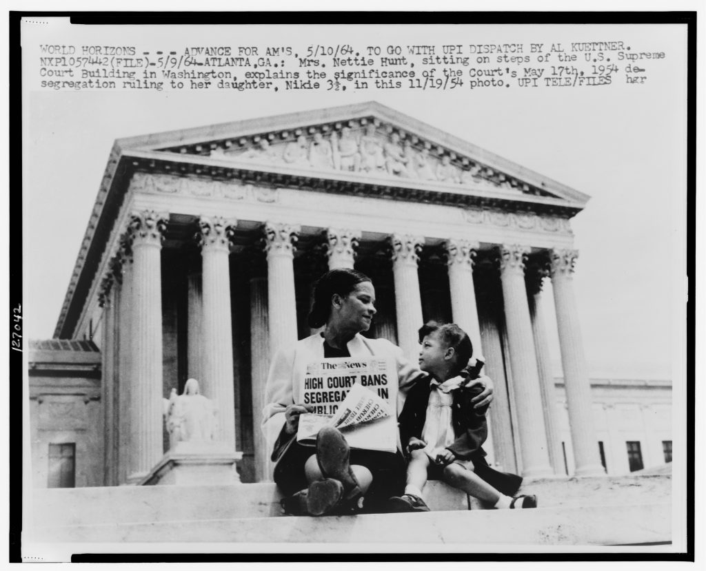 [Mrs. Nettie Hunt, sitting on steps of Supreme Court, holding newspaper, explaining to her daughter Nikie the meaning of the Supreme Court's decision banning school segregation]
