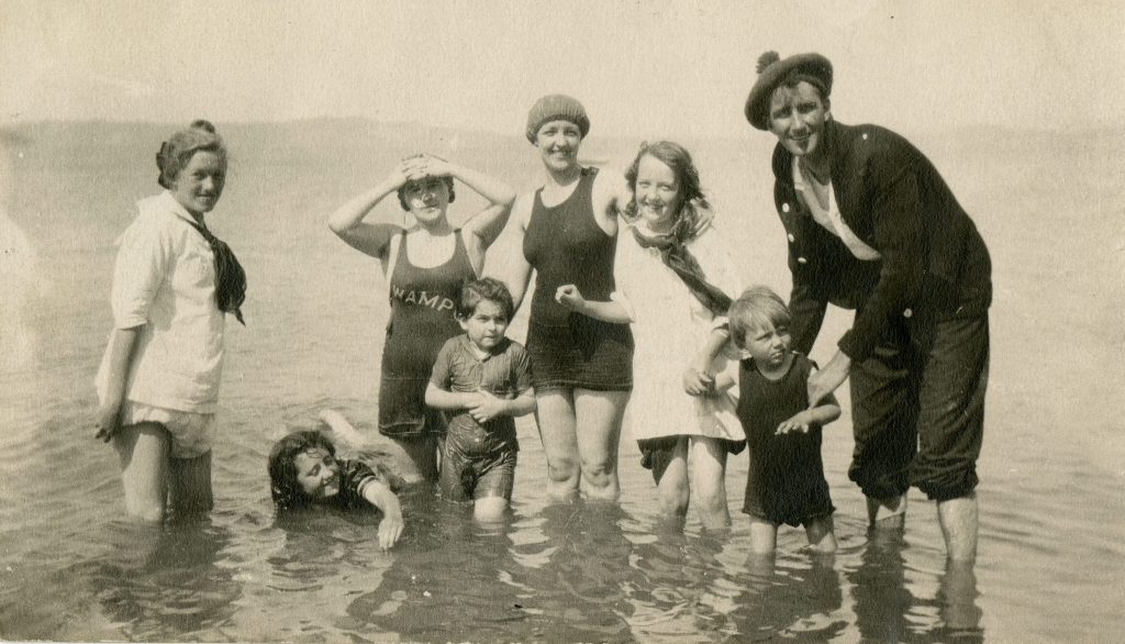 Man, women and children wading in water