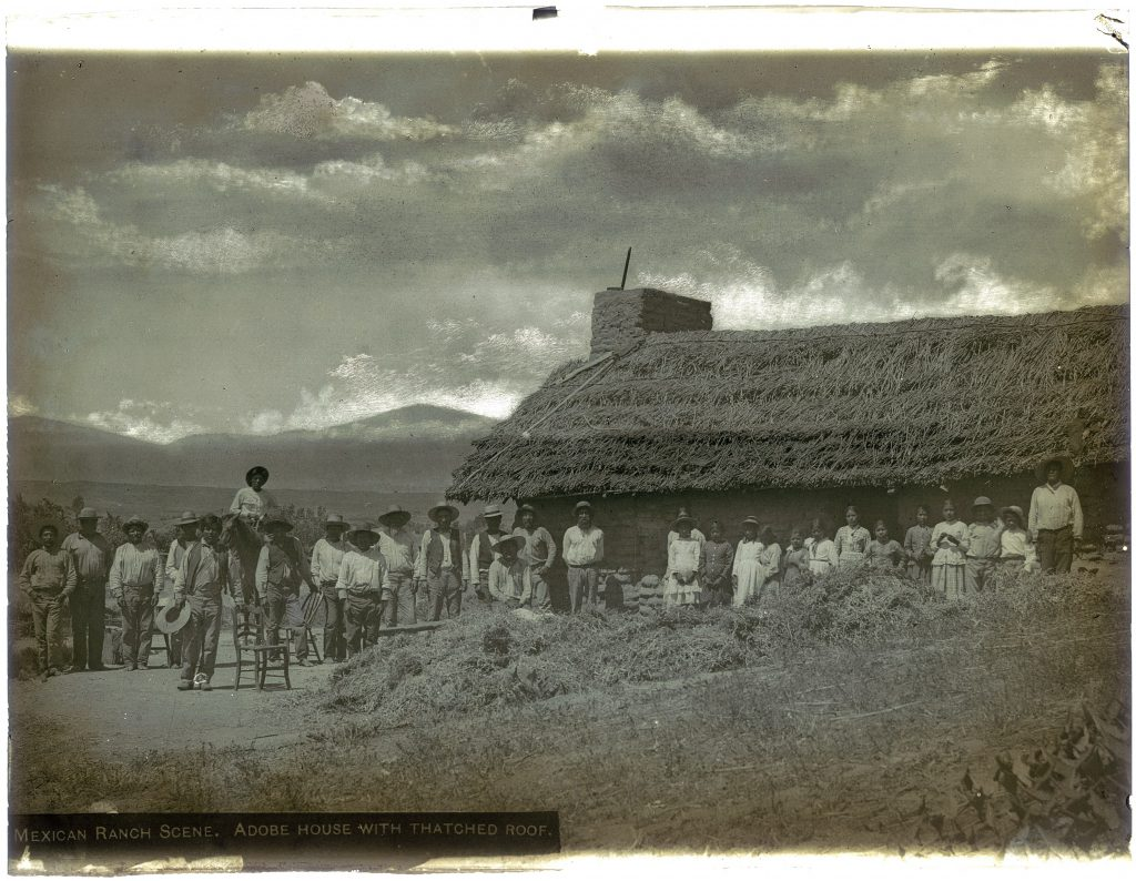 Native American sheep shearers at Rancho Camulos standing in front of an adobe building, near Piru