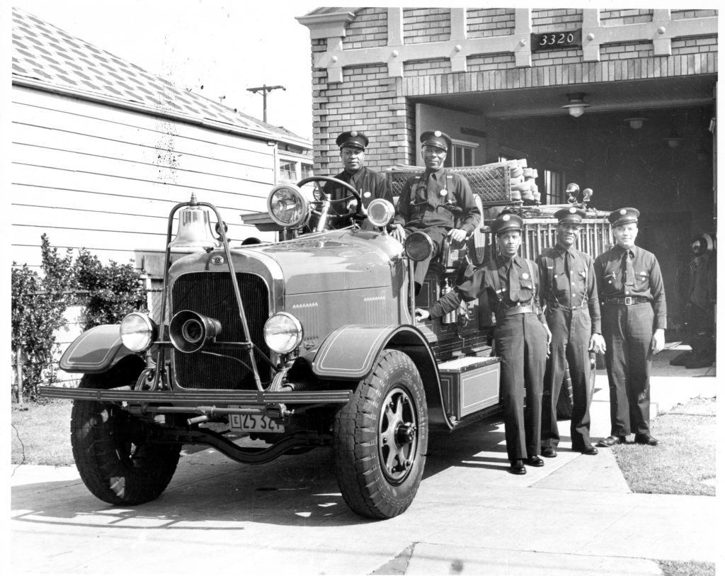 African American members of Oakland Fire Department engine company No. 22 pose with their engine in front of the fire house at 2230 Magnolia Street, Oakland, California.