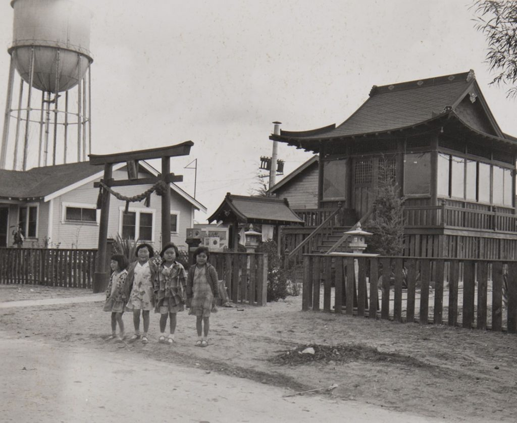 Four girls standing in front of a Buddist temple on Terminal Way, Terminal Island, Los Angeles
