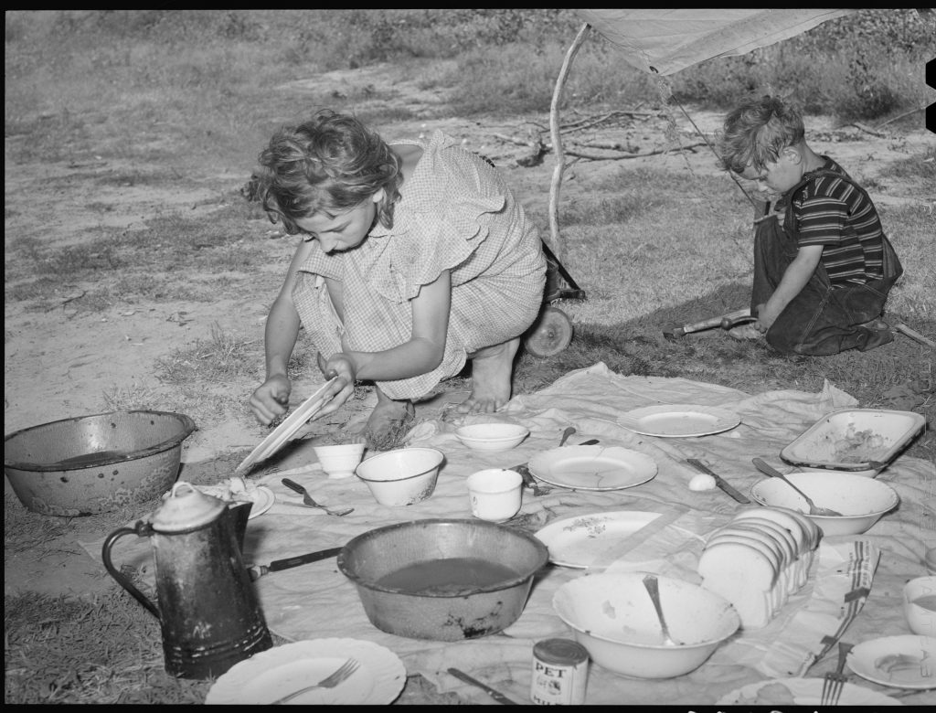 Migrant girl scraping plates after noonday meal along the highway near Muskogee, Oklahoma