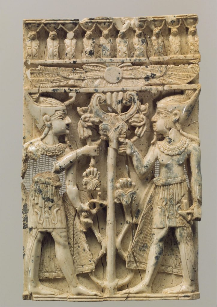 Furniture plaque carved in high relief with two Egyptianizing figures flanking a volute tree