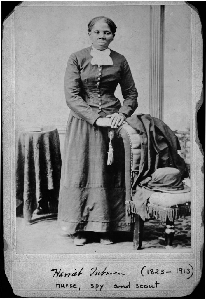 8.10.9 Harriet Tubman, full-length portrait, standing with hands on back of a chair